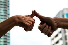 Una siluetta di due uomini che esprimono il dito del pollice e che toccano insieme Immagine Stock