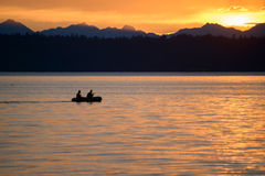 Una siluetta di due uomini che remano in una barca al tramonto Immagini Stock