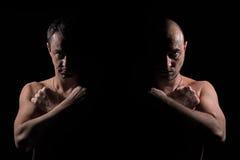 Una siluetta di due uomini seri con le mani attraversate Immagine Stock
