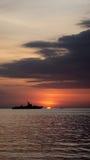 Una siluetta di tre barche con differenti dimensioni nell'oceano al crepuscolo ed al tramonto arancio Fotografia Stock