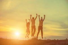 Una siluetta di tre genti che saltano insieme su al tramonto Fotografia Stock