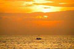 Una siluetta di tre pescatori in una barca contro il tramonto immagini stock libere da diritti