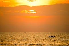 Una siluetta di tre pescatori in una barca contro il tramonto immagine stock libera da diritti