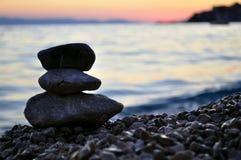 Una siluetta di tre pietre di zen sulla spiaggia al tramonto Fotografia Stock