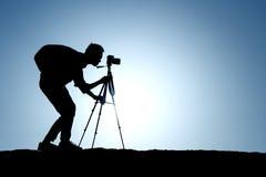 Una siluetta di un fotografo con un treppiede fotografia stock libera da diritti
