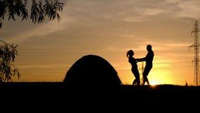Una siluetta di un giro di filatura delle coppie amorose, tenentesi per mano contro il tramonto stock footage