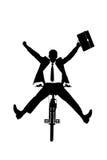 Una siluetta di un uomo d'affari felice su una bicicletta Fotografie Stock Libere da Diritti
