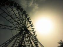 Una siluetta di una ruota panoramica al tramonto Immagini Stock Libere da Diritti