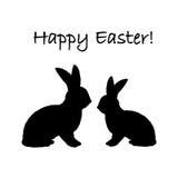 Una siluetta monocromatica di due conigli di coniglietto di pasqua. Immagini Stock