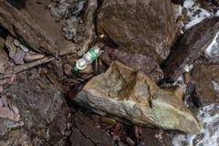 Una singola bottiglia di plastica ? lavata su fra le rocce sulla linea costiera dell'Irlanda fotografia stock