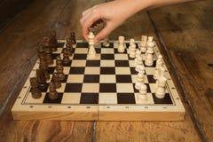 Una singola mano che gioca gli scacchi su un bordo di legno ha messo su alcuno di legno Fotografie Stock Libere da Diritti
