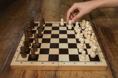 Una singola mano che gioca gli scacchi su un bordo di legno ha messo su alcuno di legno Fotografie Stock