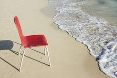 Una singola sedia rossa vuota alla spiaggia Fotografia Stock