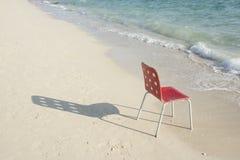 Una singola sedia rossa vuota alla spiaggia con ombra Fotografia Stock