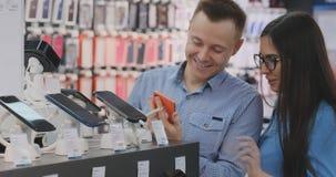 Una situación de la pareja de matrimonios cerca del escaparate con smartphones en la tienda moderna de la electrónica y elegir un almacen de video