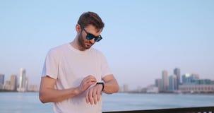 Una situaci?n del hombre joven en la costa en el verano utiliza la pantalla elegante del reloj almacen de metraje de vídeo