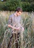 Una situación fina atractiva joven del individuo en la hierba alta en el fondo y la mirada del bosque abajo foto de archivo