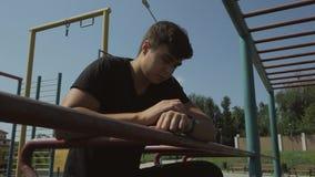 Una situación joven del individuo en el patio controla el pulso de un reloj elegante en su muñeca almacen de metraje de vídeo