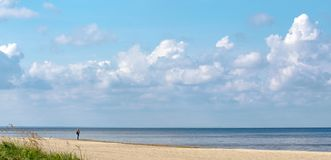 Una situación sola de la mujer en la arena en la orilla del mar Báltico y de mirar la línea del horizonte imagen de archivo