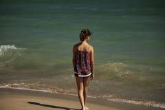 Una situaci?n bonita de la muchacha en la playa y mirada lejos en el mar, fockus suave imagen de archivo