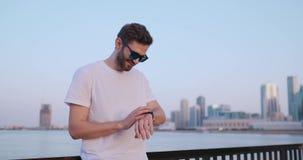 Una situaci?n del hombre joven en la costa en el verano utiliza la pantalla elegante del reloj metrajes
