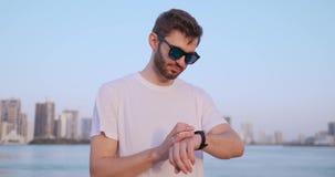Una situaci?n del hombre joven en la costa en el verano utiliza la pantalla elegante del reloj almacen de video