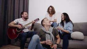 Una società di 4 amici si siede sul sofà ed ascolta il tipo che gioca la chitarra acustica Riunisca per divertirsi con video d archivio