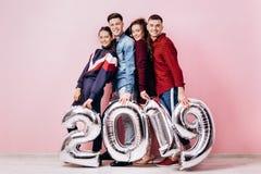 Una società felice di due ragazze e due tipi vestiti in vestiti alla moda stanno tenendo i palloni sotto forma dei numeri 2019 so fotografia stock libera da diritti