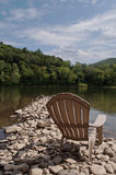 Una sola silla en la orilla del río Fotos de archivo libres de regalías