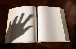 Una sombra abierta del libro y de la mano imagenes de archivo