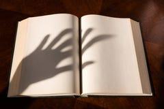 Una sombra abierta del libro y de la mano imágenes de archivo libres de regalías