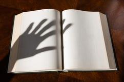 Una sombra abierta del libro y de la mano fotos de archivo
