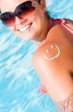 Una sonrisa hecha con el suncream en el hombro Fotografía de archivo