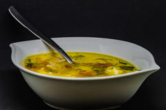 Una sopa deliciosa con las verduras y los pescados en un fondo negro Imagenes de archivo