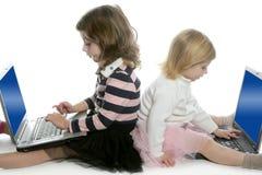 Una sorella delle due bambine con i computer portatili del calcolatore Fotografie Stock