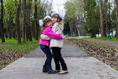 Una sorella divertente di due fratelli germani che abbraccia a vicenda mentre passeggiata in parco Divertendosi insieme, emozioni Fotografia Stock