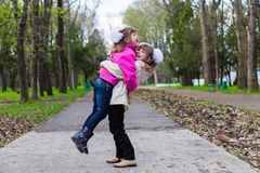 Una sorella divertente di due fratelli germani che abbraccia a vicenda mentre passeggiata in parco Divertendosi insieme, emozioni Fotografia Stock Libera da Diritti