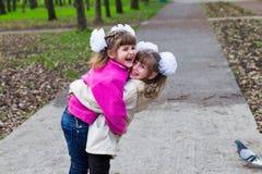 Una sorella divertente di due fratelli germani che abbraccia a vicenda mentre passeggiata in parco Divertendosi insieme, emozioni Immagini Stock
