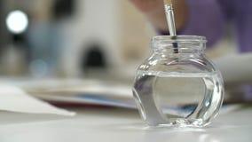 Una spazzola con pittura è immersa in acqua e la pittura si sparge nell'acqua stock footage