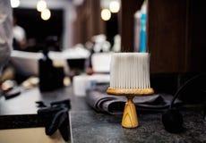 Una spazzola della polvere dei capelli ed altri strumenti nel salone di capelli per gli uomini, interno del parrucchiere fotografie stock