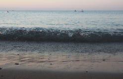 Una spiaggia calma ed abbandonata, onde calde delicate che strisciano lentamente fuori sulla riva immagine stock libera da diritti