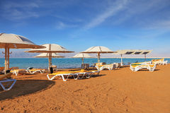 Una spiaggia con gli ombrelli di spiaggia ed i loungers della spiaggia fotografia stock libera da diritti