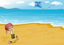 Una spiaggia con un gioco del ragazzo Immagini Stock