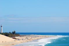 Una spiaggia di sabbia soleggiata che è colpita delicatamente dalle creste dell'onda spumose, con un faro che sta su un sacchetto  Immagini Stock Libere da Diritti