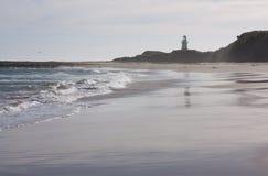 Una spiaggia e un faro nella distanza al punto di Waipapa nel Catlins nell'isola del sud in Nuova Zelanda fotografia stock