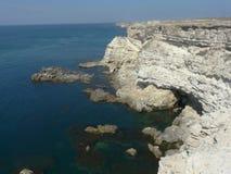 Una spiaggia vuota e di pietra delle rocce grige, con un'alta scogliera sopra un mare profondo e scuro Fotografie Stock Libere da Diritti