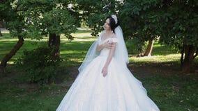 Una sposa molto bella sta da solo nel parco, preoccupazioni mentre aspetta lo sposo archivi video