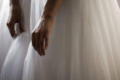 Una sposa in un bello bordo del vestito dalla tenuta del vestito da sposa immagine stock