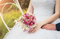 Una sposa in un vestito da sposa bianco sta tenendo un mazzo in sue mani Primo piano, fuoco selettivo fotografia stock libera da diritti