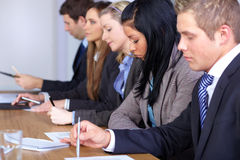 Una squadra di 5 genti che si siedono alla tabella di congresso Fotografie Stock Libere da Diritti